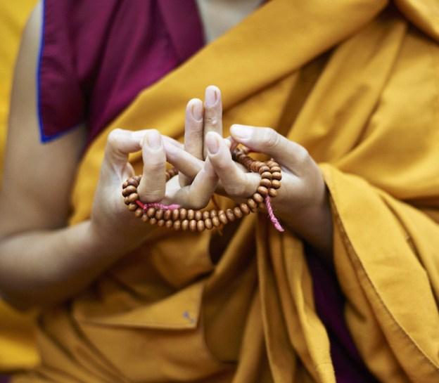 Una monaca buddista tibetana esegue il Mandala Mudra con il suo mala (perline di preghiera buddista). Foto per gentile concessione di Olivier Adam